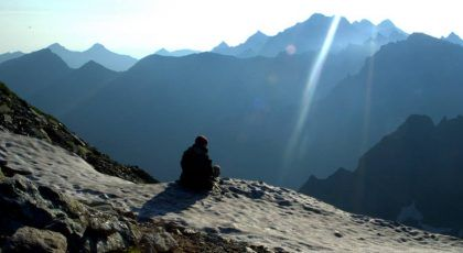 A man sitting on a cliff in snowy high mountains during dawn