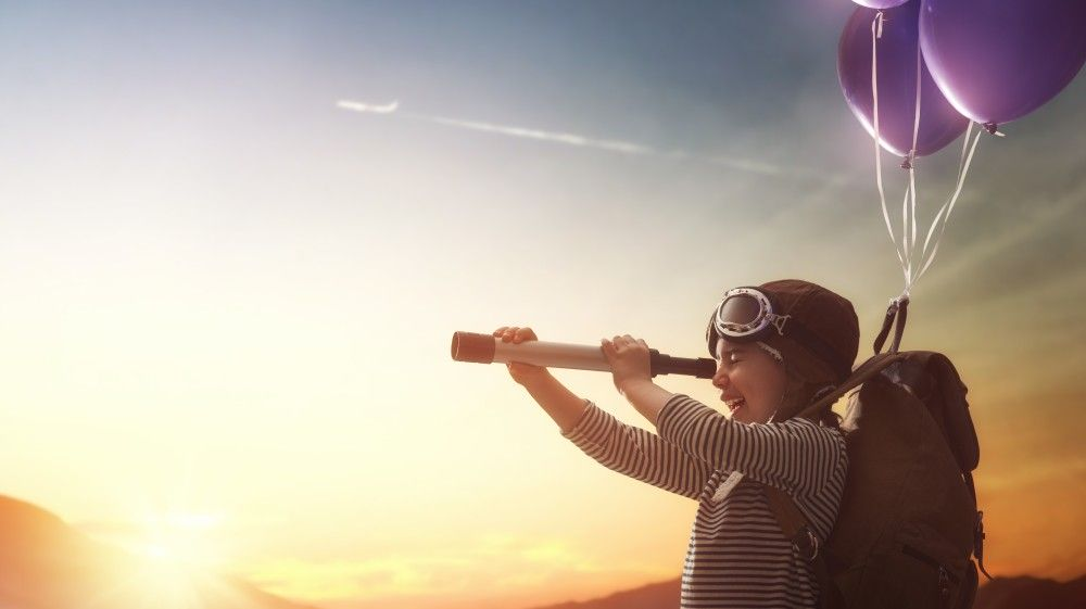 A boy flying through the air attached to baloons, looking through a scope