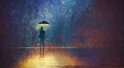 Illuminated girl under a glowing umbrella among a dark gloomy scenery
