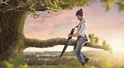 A man cutting the branch under himself